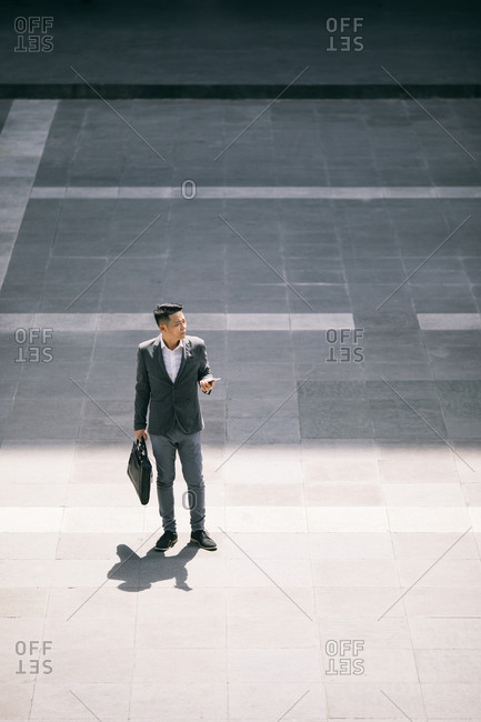 Middle-aged Asian businessman standing  outdoors and holding his cell phone and a bag.