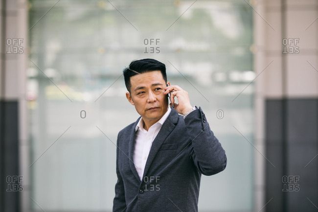 Middle-aged Asian businessman standing  outdoors and talking on his cell phone.