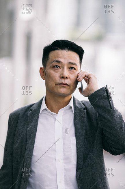 Portrait of serious Asian middle-aged businessman standing outdoors and talking on a cell phone.
