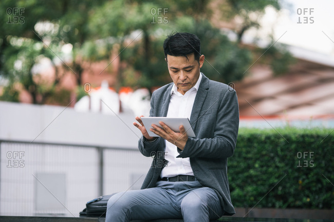 Serious Asian middle-aged businessman sitting outdoors and working on his tablet.