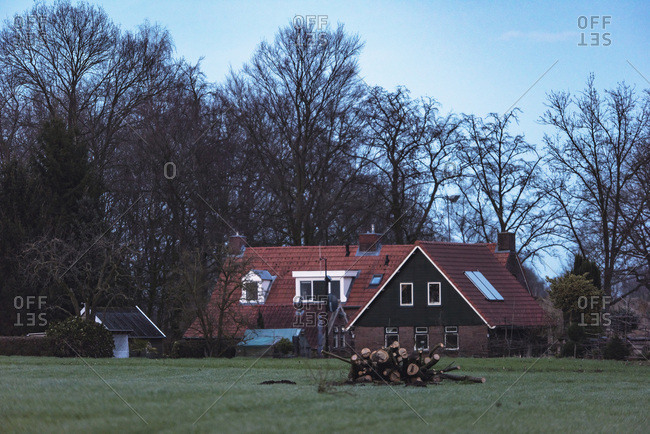 Pile of firewood in field outside rural house