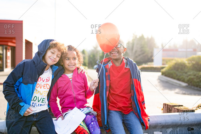 Little girl sitting net to brothers holding a balloon