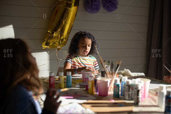 Little girl painting at birthday party