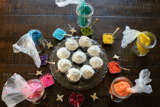 Overhead view of cupcakes ready to be decorated with colorful toppings