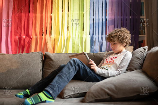 Young boy playing tablet in front of rainbow streamers