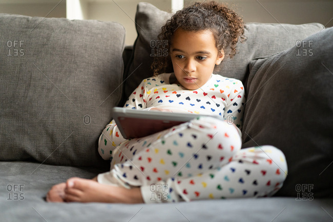 Close up of girl wearing rainbow heart pajamas playing tablet