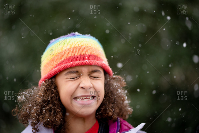 Little girl closing her eyes as snowflakes fall