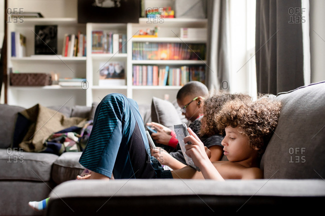 Three kids sitting on sofa playing on their tablets