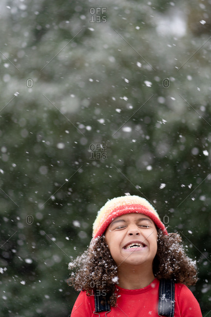 Girl closing her eyes as snowflakes fall