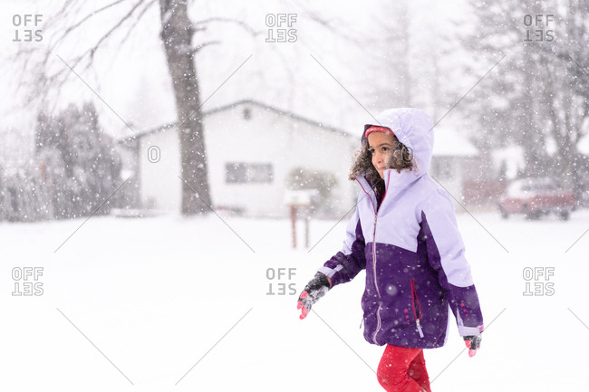 Little girl walking outside in the snow