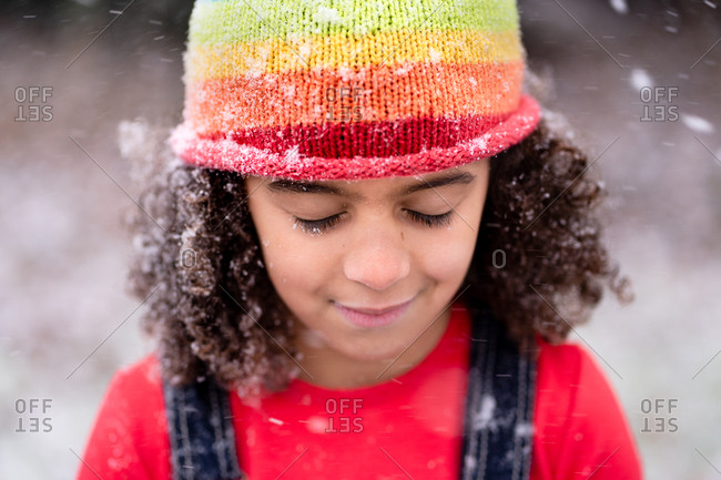 Close up of little girl closing her eyes as snowflakes fall