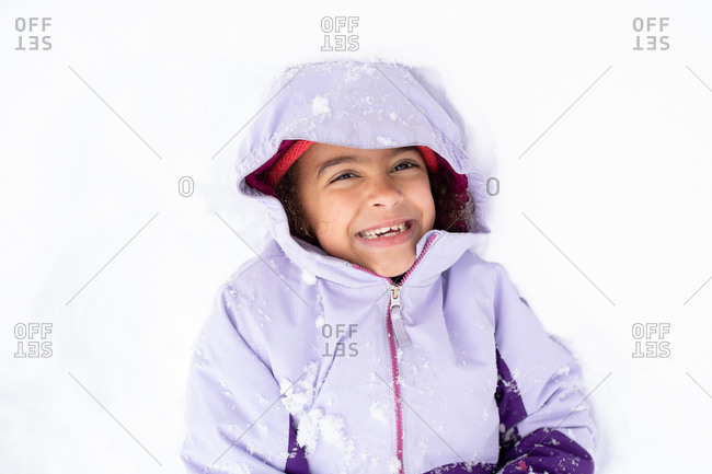 Little girl lying outside in the snow