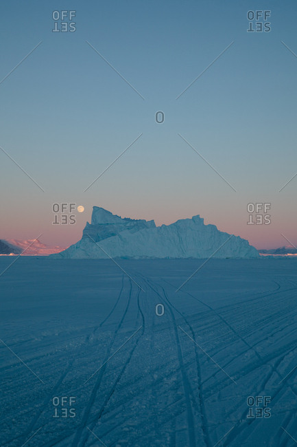 Moon going down behind icebergs in Greenland