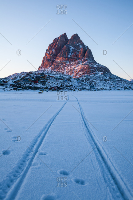 Tire tracks leading to a mountain in Greenland at sunrise