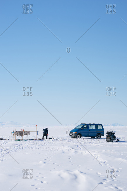 Greenland - April 9, 2017: Person ice fishing in rural Greenland