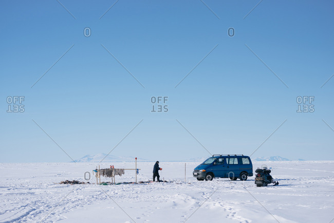 Greenland - April 9, 2017: Person ice fishing