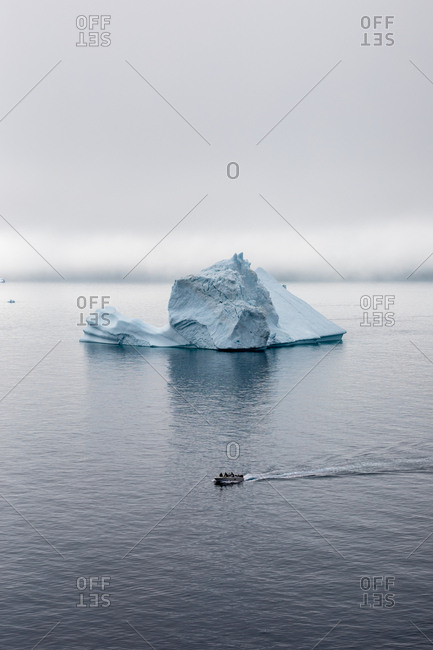 Small boat moving past iceberg in the sea