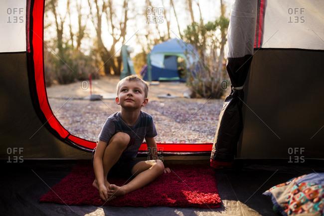 Boy sits inside tent