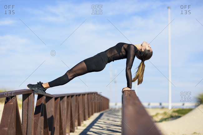 Sportive woman exercising on railing of a wooden bridge