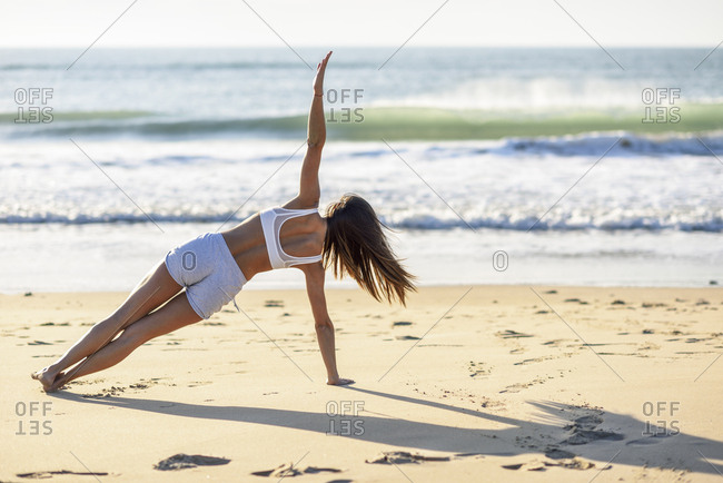 Sportive woman exercising on the beach