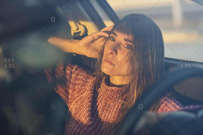 Portrait of serious woman sitting in car at sunset