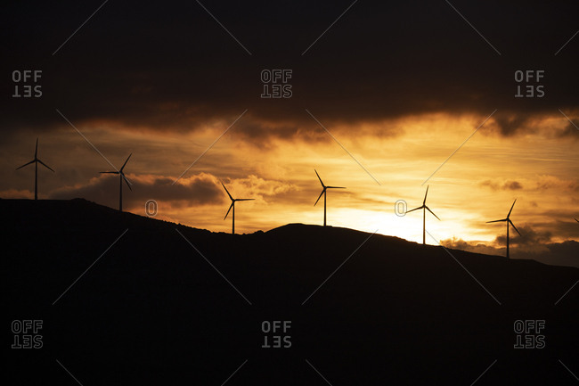 Spain- Andalusia- Tarifa- wind wheels on mountain at sunrise