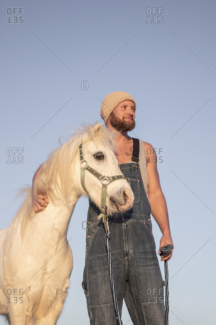 Smiling man with pony under blue sky