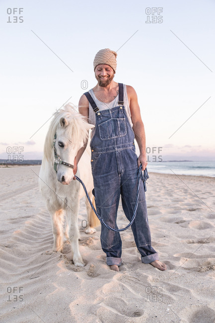 Spain- Tarifa- smiling man with pony standing on the beach