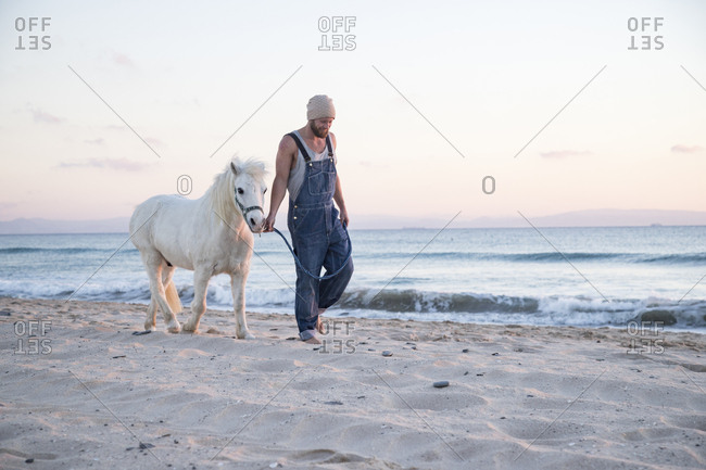 Spain- Tarifa- man walking with pony on the beach
