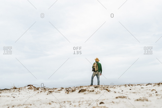 Australia- Tasmania- Maria Island- back view of man with backpack on the beach looking at distance