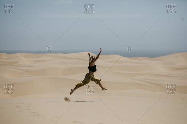 Namibia- Walvis Bay- Namib-Naukluft National Park- Sandwich Harbour- woman jumping in dune landscape