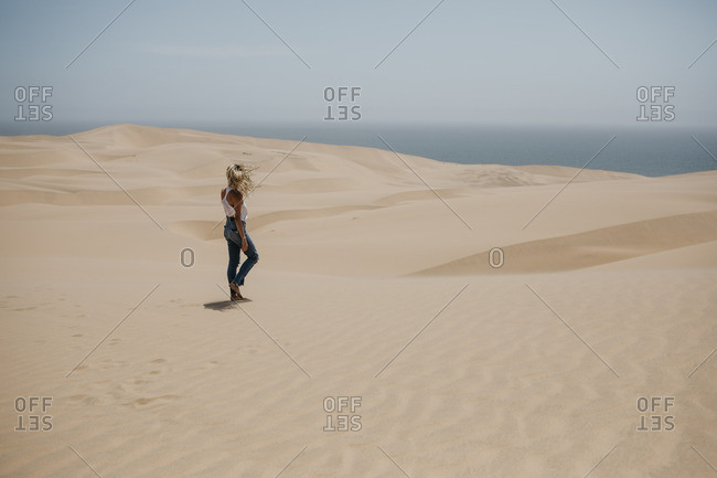 Namibia- Walvis Bay- Namib-Naukluft National Park- Sandwich Harbour- woman walking in dune landscape