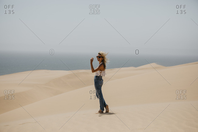 Namibia- Walvis Bay- Namib-Naukluft National Park- Sandwich Harbour- happy woman in dune landscape