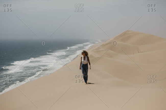 Namibia- Walvis Bay- Namib-Naukluft National Park- Sandwich Harbour- woman walking in dune landscape at the sea