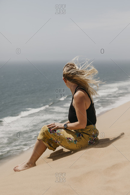 Namibia- Walvis Bay- Namib-Naukluft National Park- Sandwich Harbour- woman sitting in dune landscape at the sea