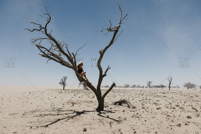 Namibia- Way to Sossusvlei- woman sitting in dead tree in the desert