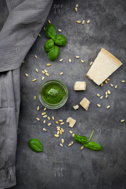 Glass of homemade pesto Genovese- pine nuts- basil leaves and parmesan on grey ground