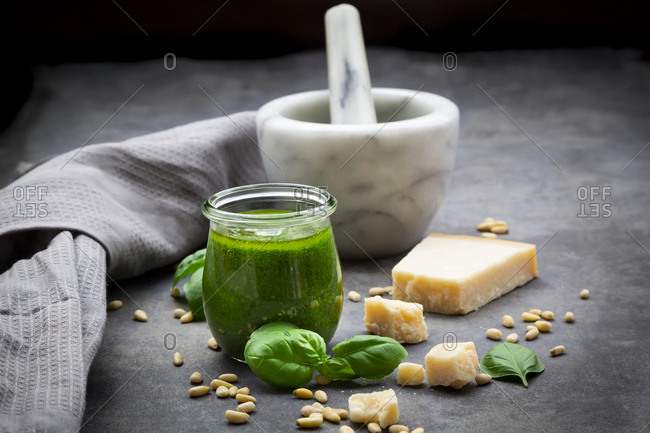 Glass of homemade pesto Genovese- ingredients- mortar and kitchen towel