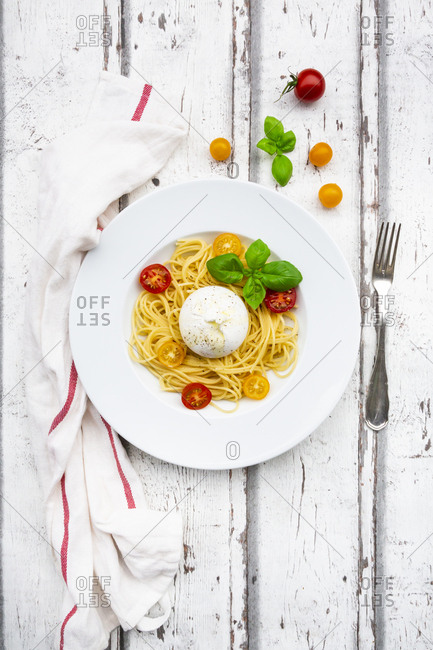 Spaghetti with tomatoes- burrata and basil leaves