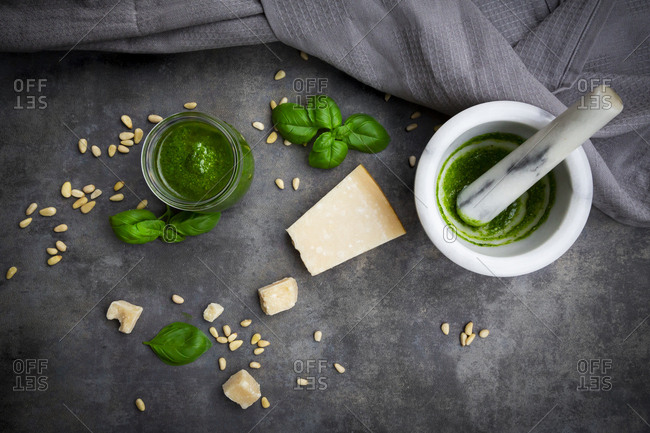 Glass of homemade pesto Genovese- mortar and ingredients on grey ground