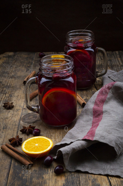 Glasses of mulled wine with cranberries- cinnamon sticks- orange and star anise on dark wood
