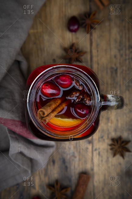 Glass of mulled wine with cranberries- cinnamon sticks- orange and star anise on dark wood- focus on foreground