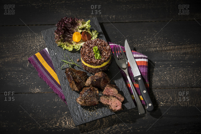 Kangaroo steak with red rice and mango on slate plate