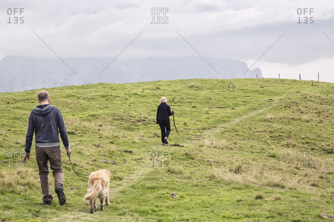Austria- Tyrol- Kaiser mountains- mother and adult son with dog on a hiking trip in the mountains