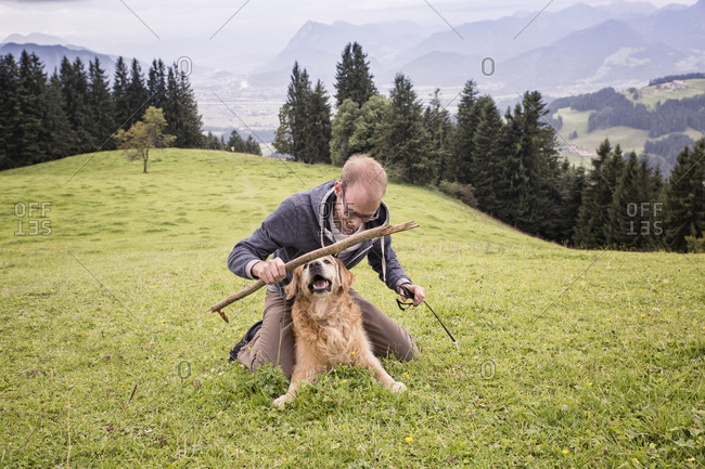 Austria- Tyrol- Kaiser mountains- man playing with dog on alpine meadow