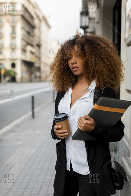 Young woman with laptop bag and coffee to go in the city