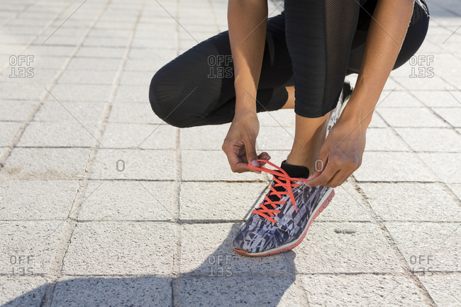 Close-up of young woman tying her shoes before workout