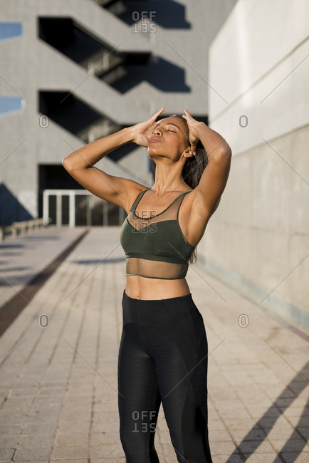 Sporty young woman having a break during workout in the city