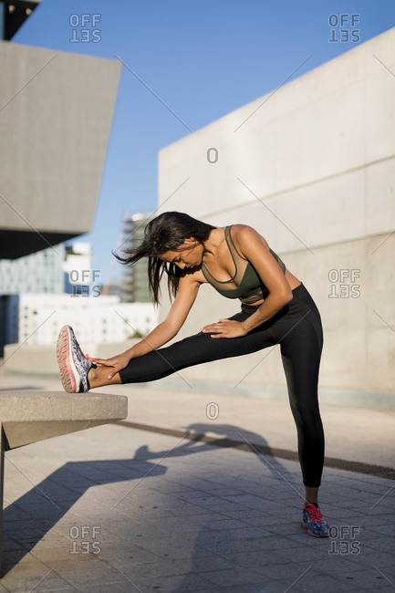 Young woman doing stretching exercise in the city