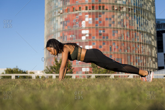 Young woman doing pushups in the city